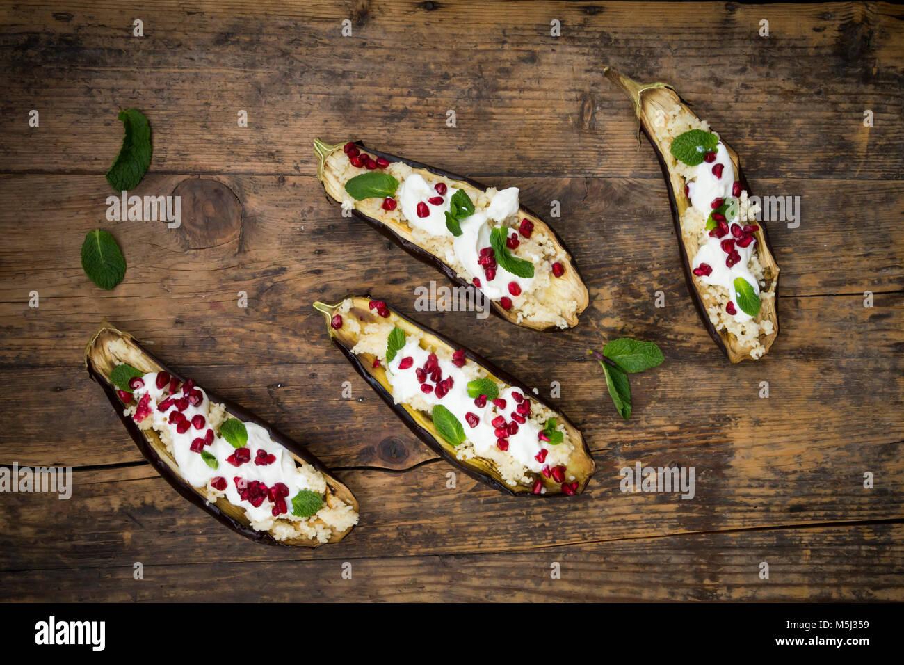 Gefüllte Aubergine, Couscous, Joghurt Sauce, Minze und Granatapfel Samen Stockbild