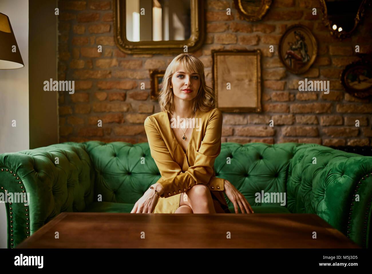 Portrait von eleganten Frau sitzt auf einer Couch Stockbild