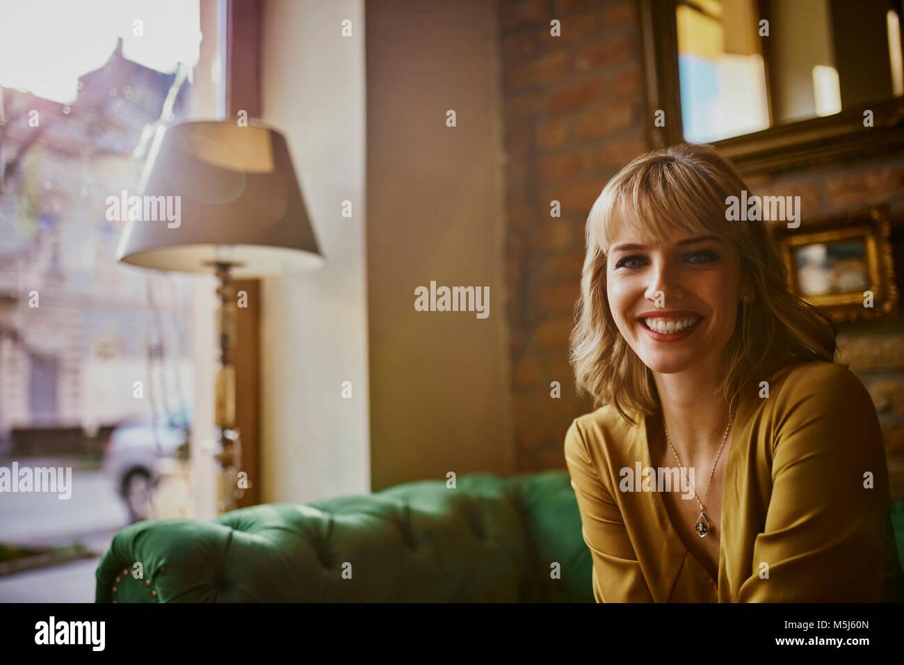Portrait von lächelnden elegante Frau sitzt auf einer Couch Stockbild