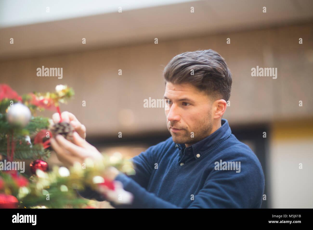 Porträt der Mann an Weihnachten Dekoration in einem Einkaufszentrum auf der Suche Stockbild