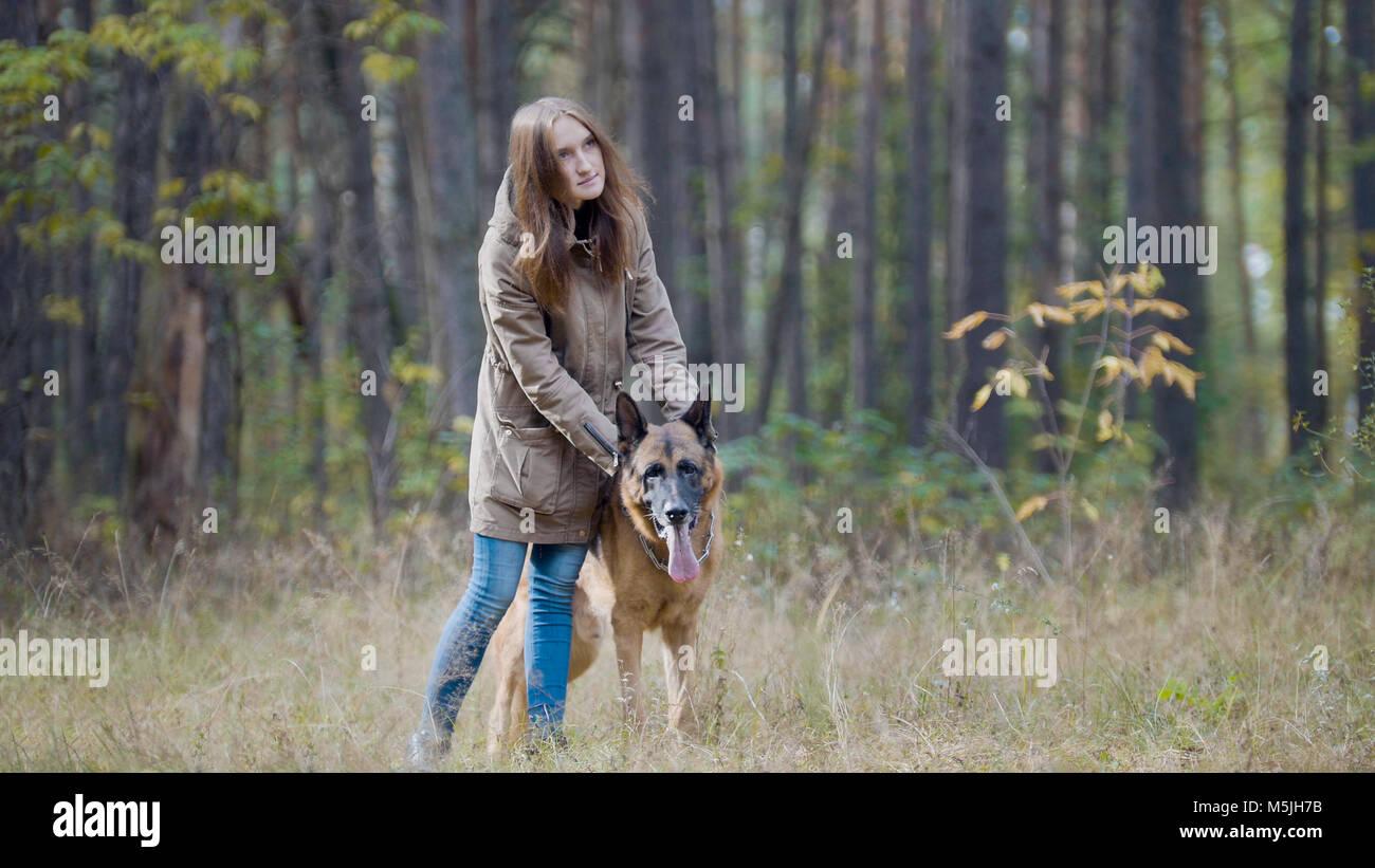 Blondes Haar Frauen spielen mit ihrem Haustier - Deutscher Schäferhund - zu Fuß auf einem Herbst Wald Stockfoto