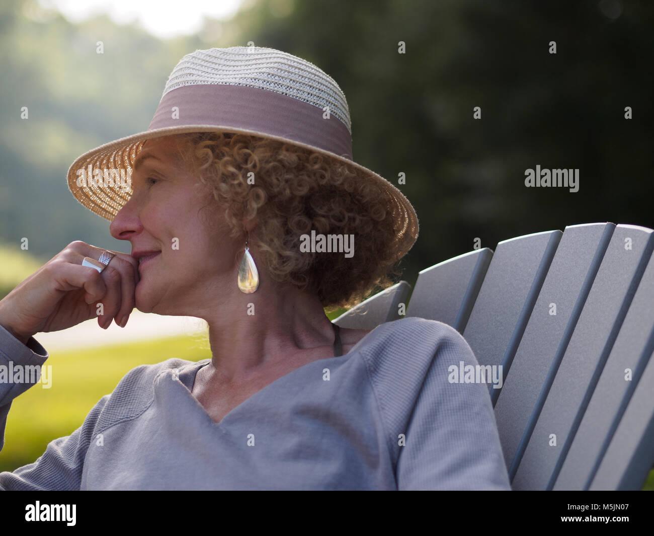 Ältere Frau mit Hut in der Adirondack Stuhl nachdenken Leben sitzen Stockbild