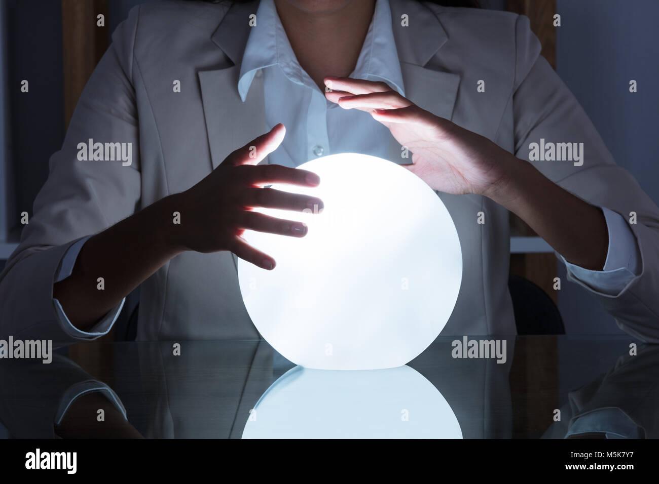 Nahaufnahme der Geschäftsfrau Hand auf Crystal Ball am Tisch im Büro Stockbild