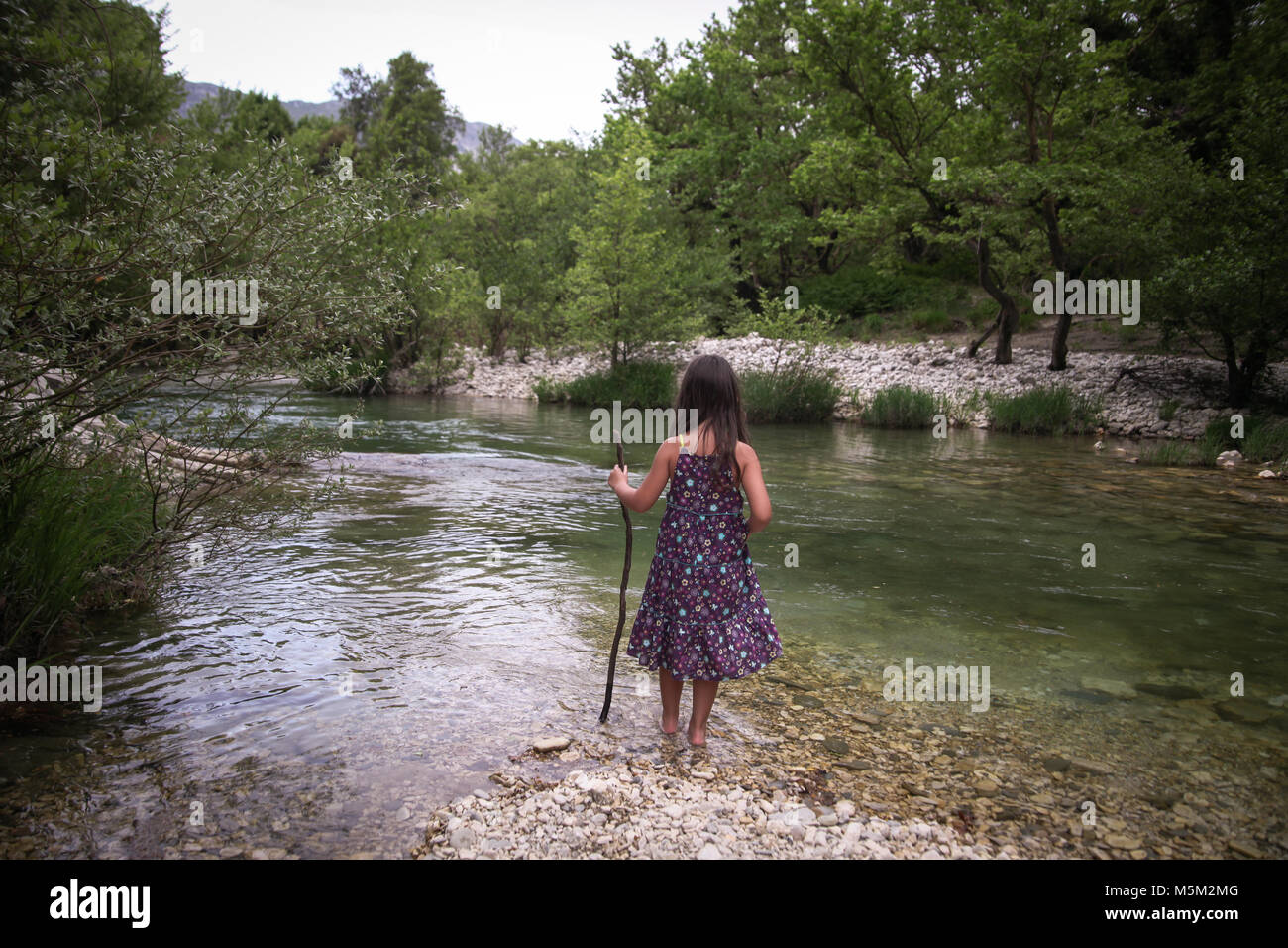 Ein kleines Mädchen mit einem Lila gepunkteten Kleid, mit einem Stick ist zu Fuß in den Fluss Acheron, Stockbild