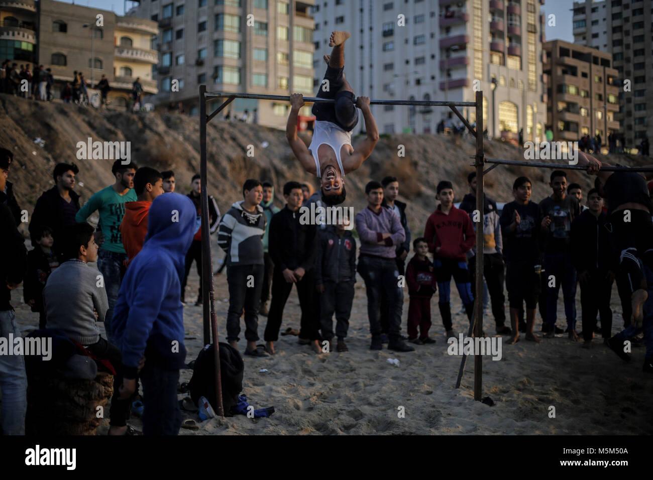 Gaza, Gaza. 23 Feb, 2018. Palästinenser beobachten, wie eine Jugend Praktiken seiner parkour Fähigkeiten Stockbild