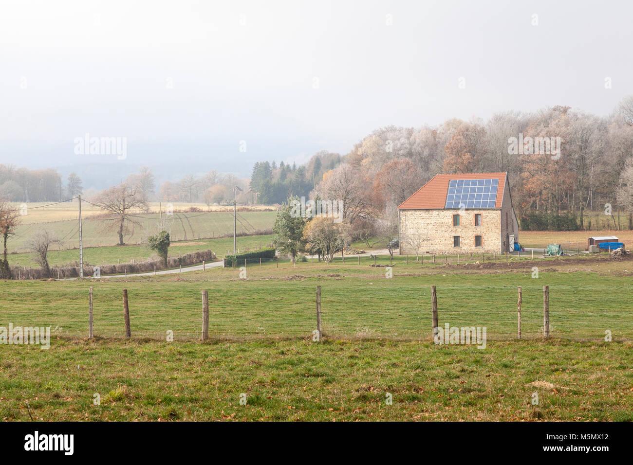 Bauernhaus mit Photovoltaik Solar Panels in einem eiskalten misty Winterlandschaft in der Creuse, Nouvelle-Aquitaine, Stockbild