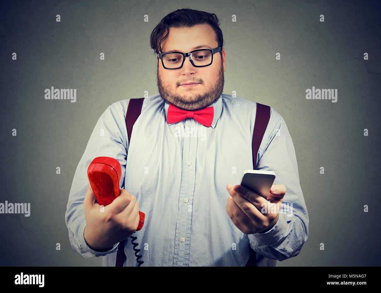 Junger Mann in formalen Outfit suchen verwundert über altmodische und zeitgenössische Gadgets. Stockbild