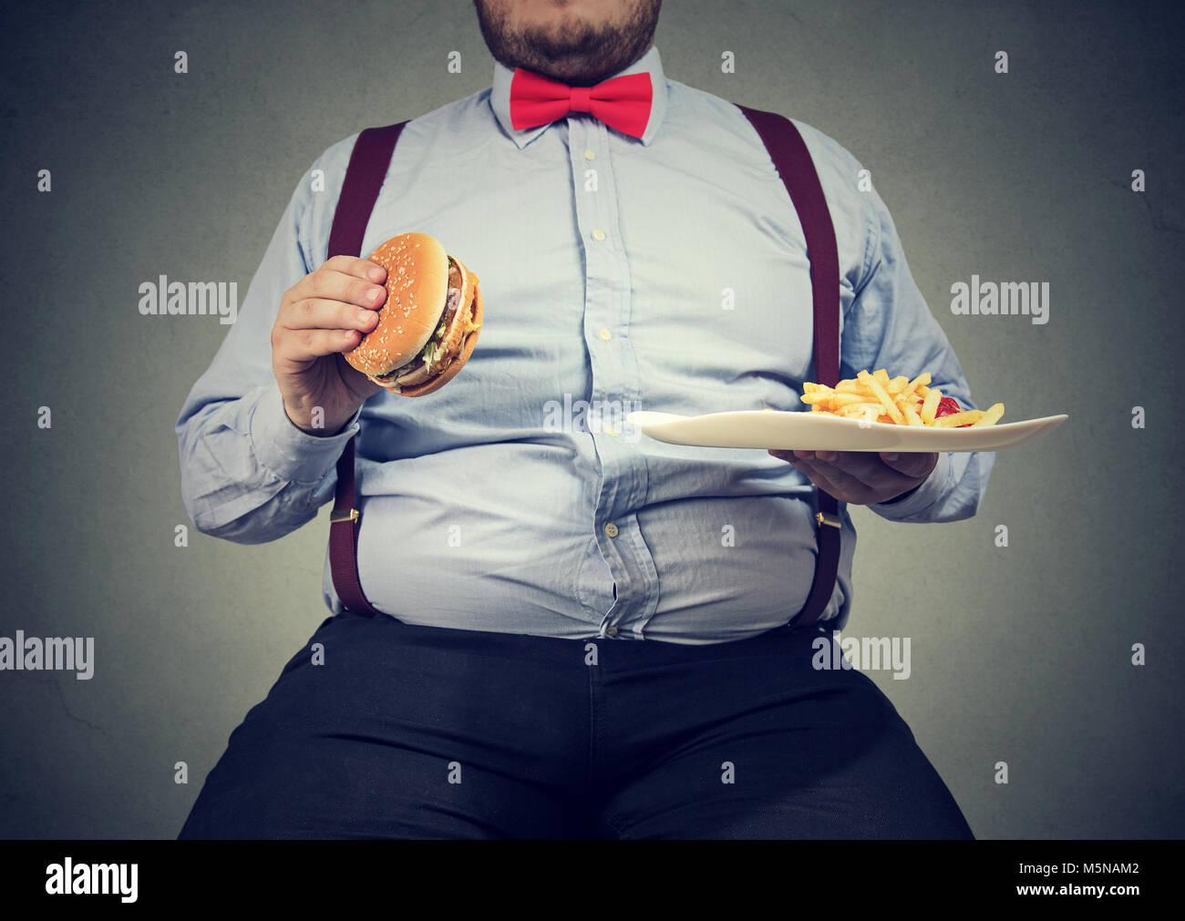 Erntegut Schuß von großer Mann in formelle Kleidung sitzen und konsumieren Platte mit Fast-food auf Grau. Stockbild