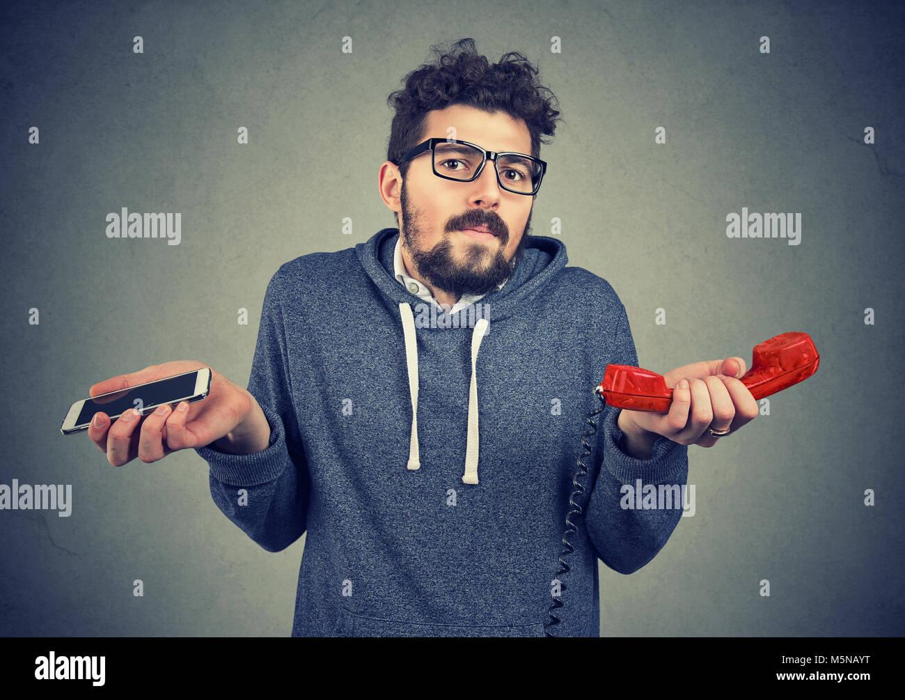 Junge legerer Mann schaut ratlos über die altmodische und zeitgenössische Gadgets. Stockbild