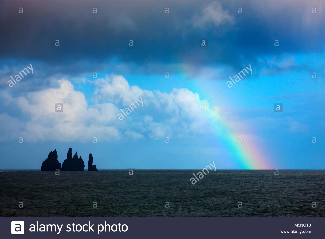Ein Regenbogen beginnt vom Atlantischen Ozean, nicht weit von Reynisdrangar Meer Strand Reynisfjara Stapel gerade Stockbild
