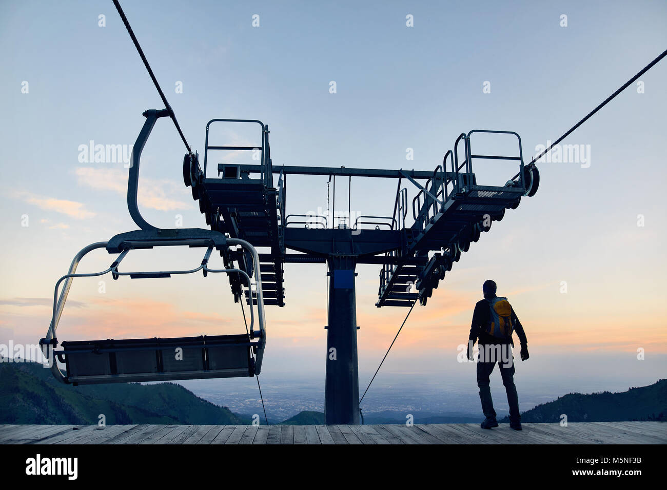 Touristische Mann am Ski Lift Station in Silhouette hoch in Mountain Ski Resort bei Sonnenaufgang Stockfoto