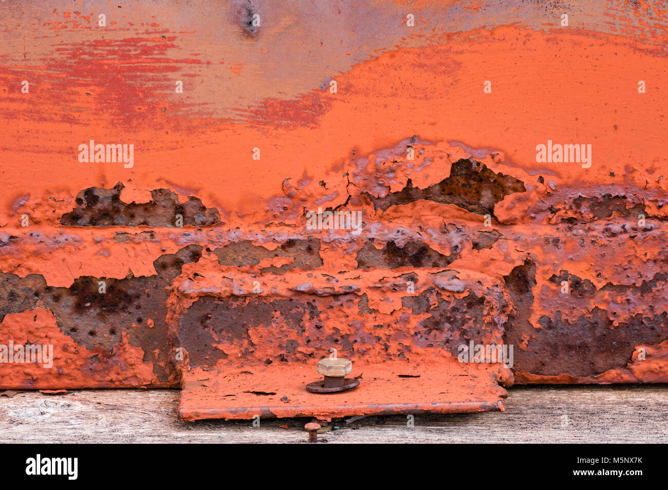 Orange lackiertem Metall mit abblätternder Farbe und Rost zu einer ...