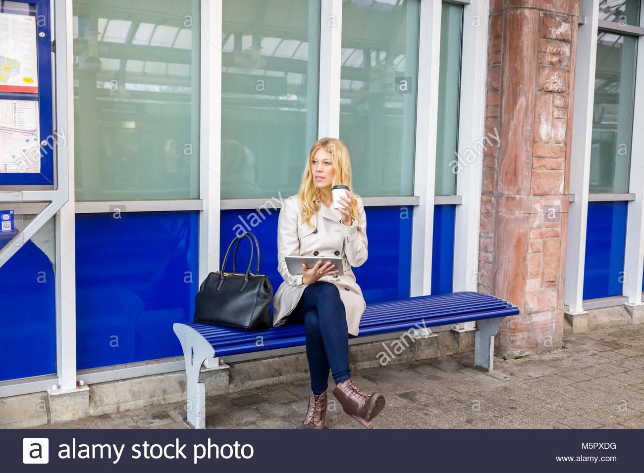 Junge Frau sitzt auf einer Bank warten Stockbild