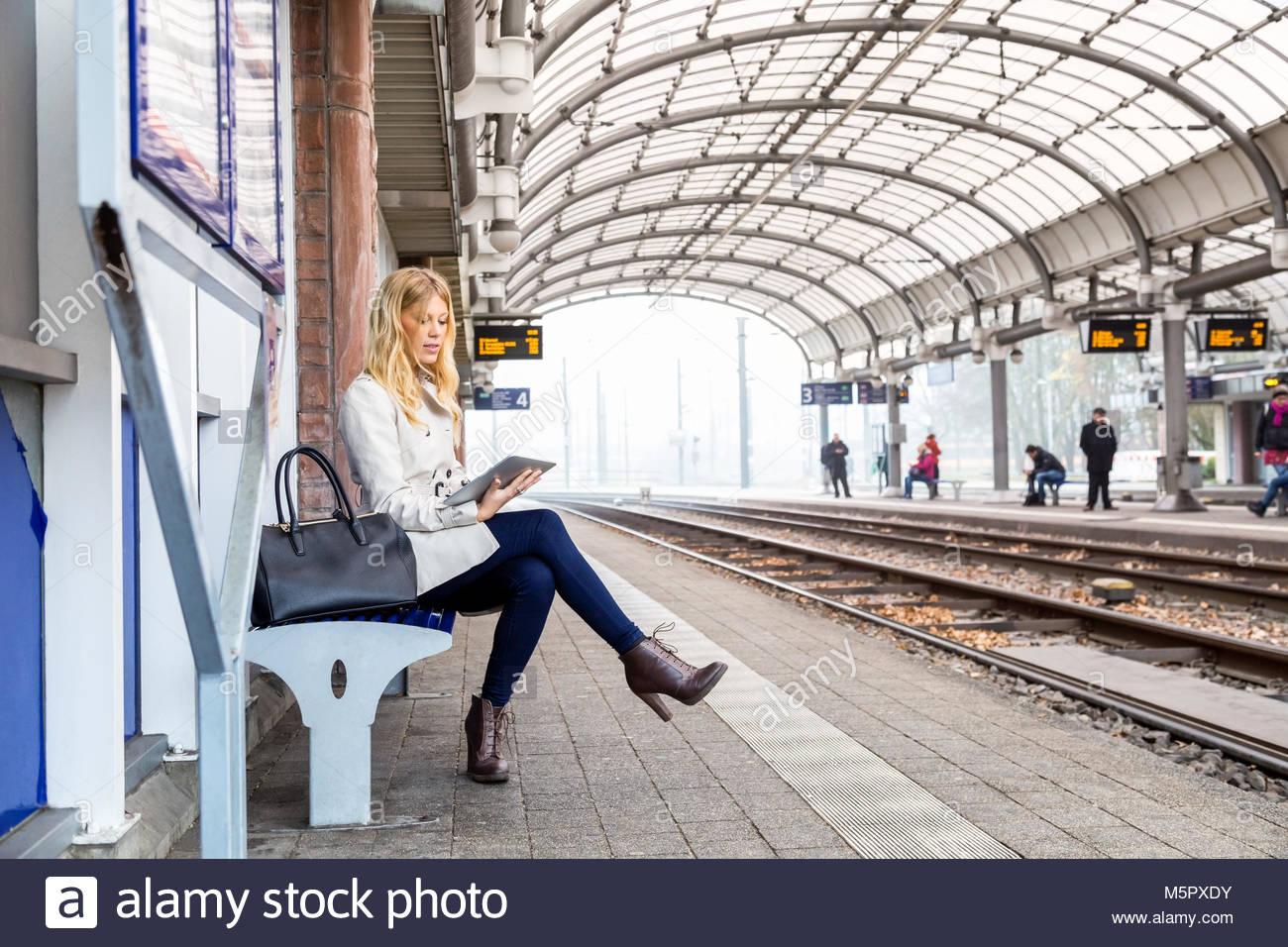 Attraktive junge Frau warten auf einen Zug Stockbild