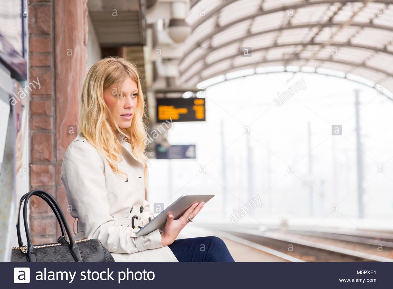Attraktive junge Frau warten auf einen Zug Stockfoto