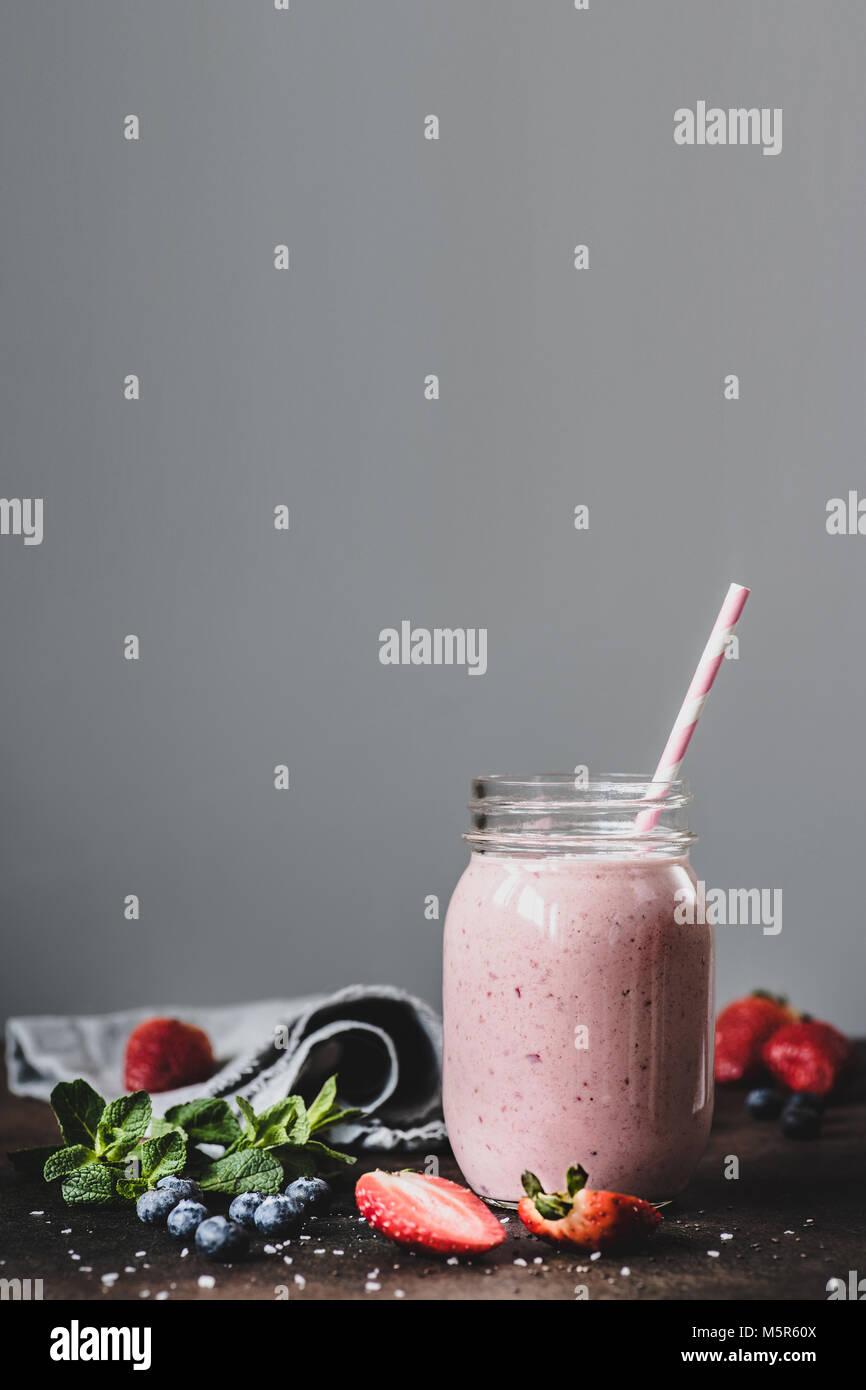 Rosa strawbery Smoothie in Glas mit Strohhalm auf grauem Hintergrund. Kopieren Sie Platz für Text, getönten Stockbild