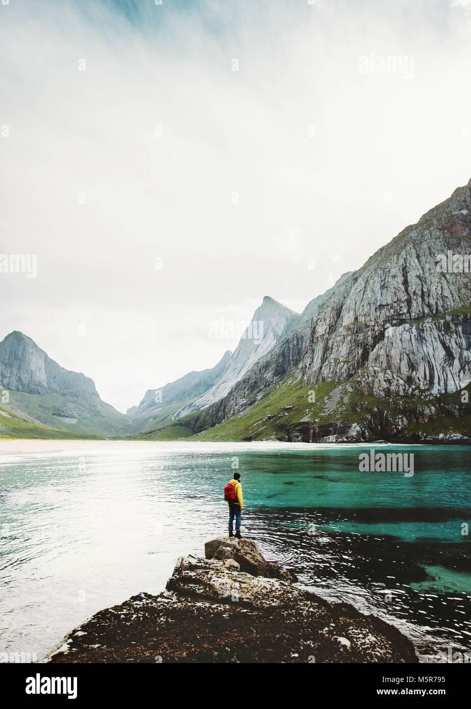 Mann Backpacker allein auf See Stein in Norwegen Reisen Lifestyle überleben emotionale Konzept Abenteuer Outdoor Stockbild