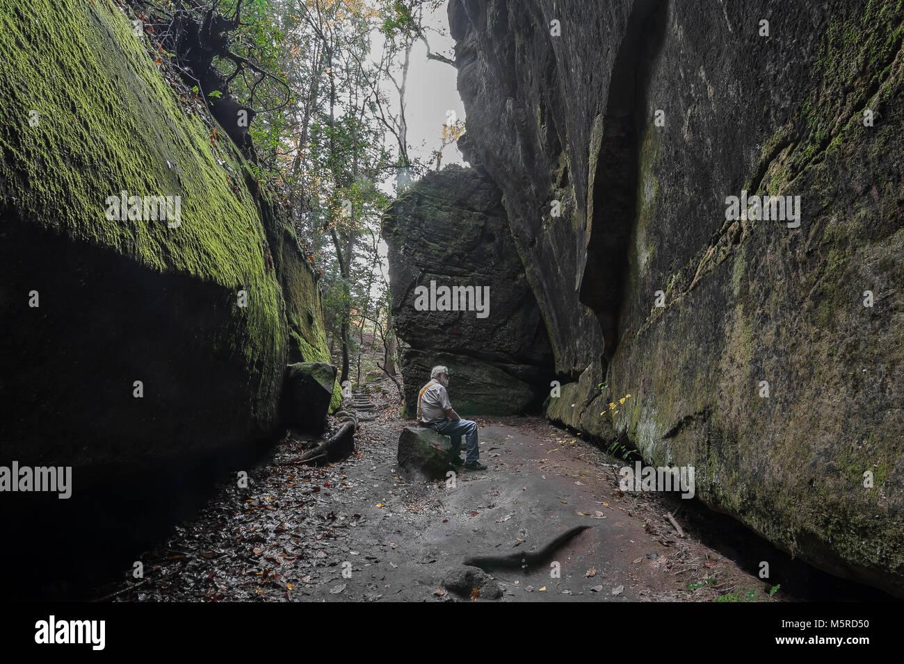 Ein Mensch sitzt und grübelt über Leben, während sie durch Felswände an Dismals Canyon in Franklin Stockbild
