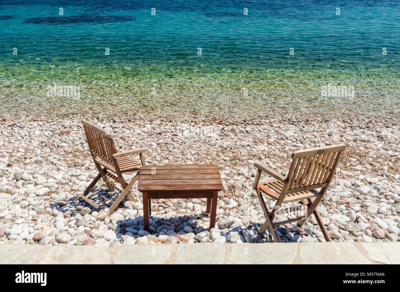 Tisch und Stühle auf den Stein Strand von Livadia, Tilos Island, Griechenland Stockbild