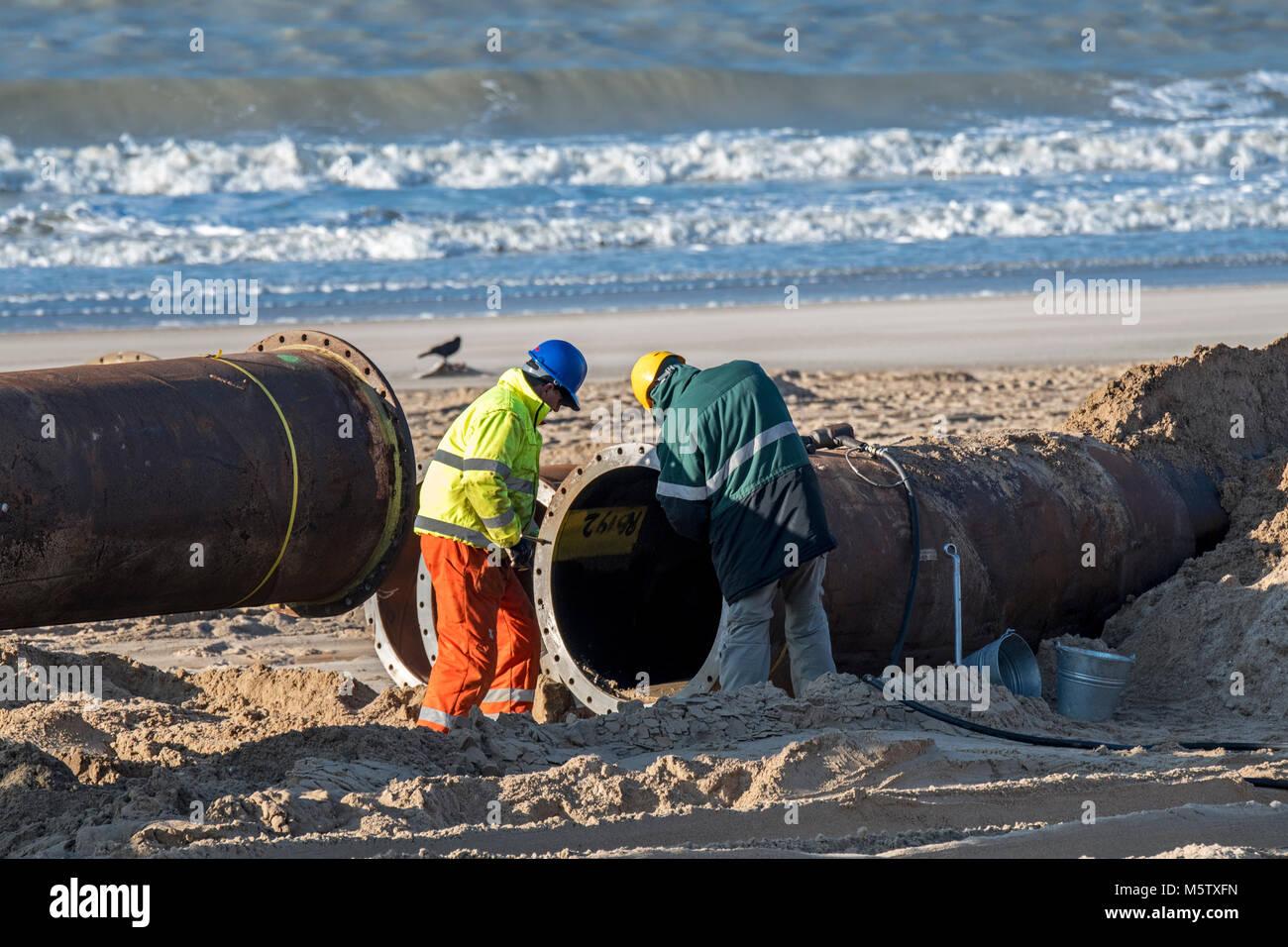 Baggerarbeiten Mitarbeiter, die Rohre der Pipeline Während sand Auffüllen/Strand Nahrung arbeitet an der Stockbild