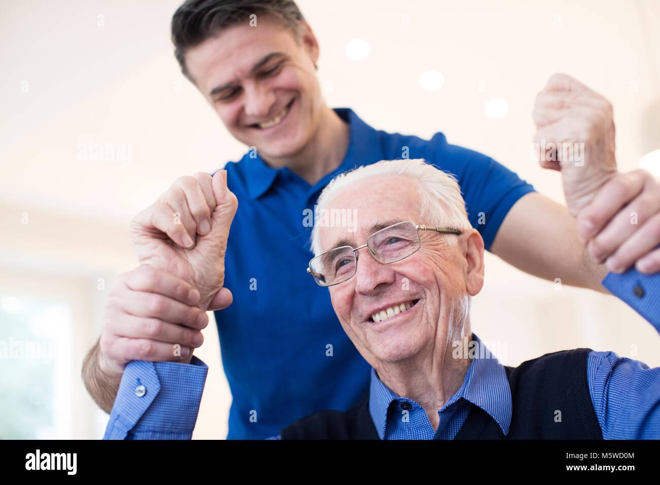 Männliche Krankenschwester Bewertung Senior Schlaganfall Opfer durch Anheben der Arme Stockbild