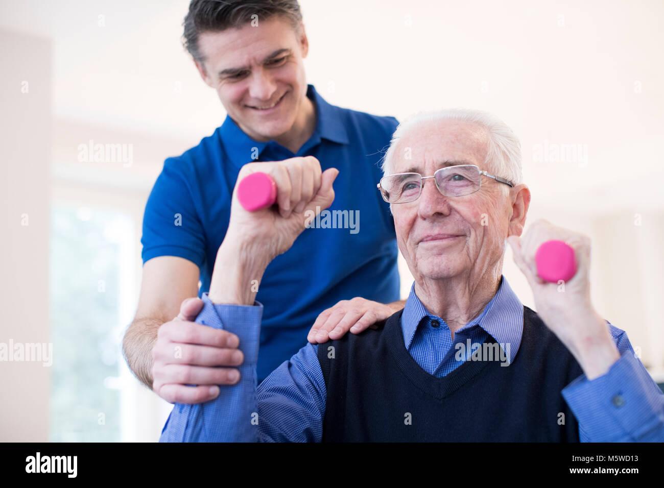Physiotherapeuten helfen Denopr Mann zu heben Trainingshanteln Stockbild