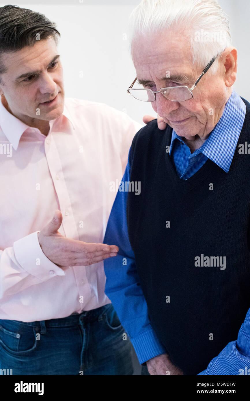 Verwirrt älterer Mann mit erwachsenen Sohn zu Hause Stockbild
