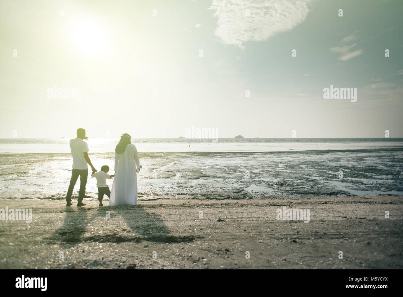 Eine Familie ist, die schöne Aussicht auf den Sonnenuntergang am Strand. familiäre Beziehung bonding Konzept. Stockbild