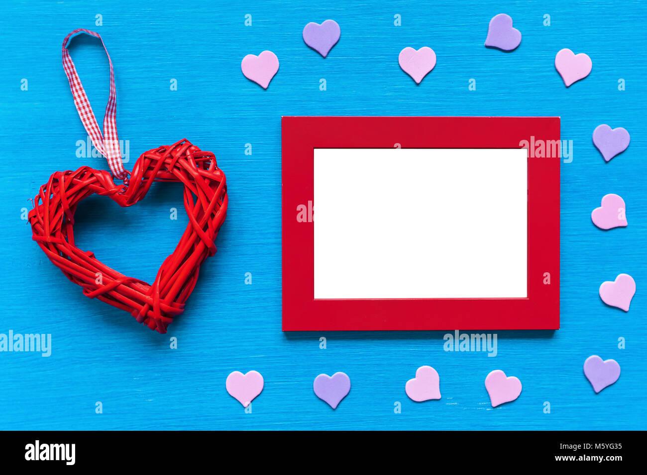 Roter Rahmen und das Herz liegt auf einem türkisfarbenen Tisch ...
