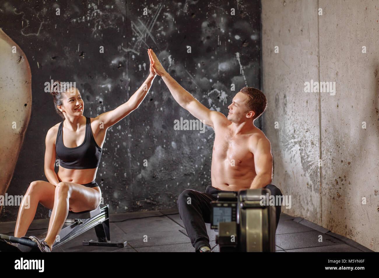 Der Mann und die Frau eine hohe - fünf während der Übungen mit Rudergerät Stockfoto