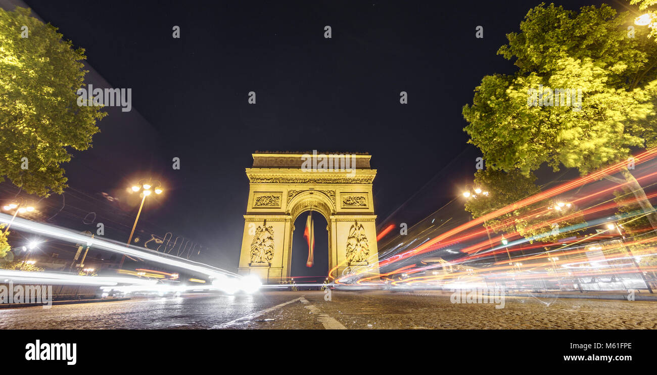 Beeindruckender Triumphbogen und Auto Lichter in der Nacht Stockbild