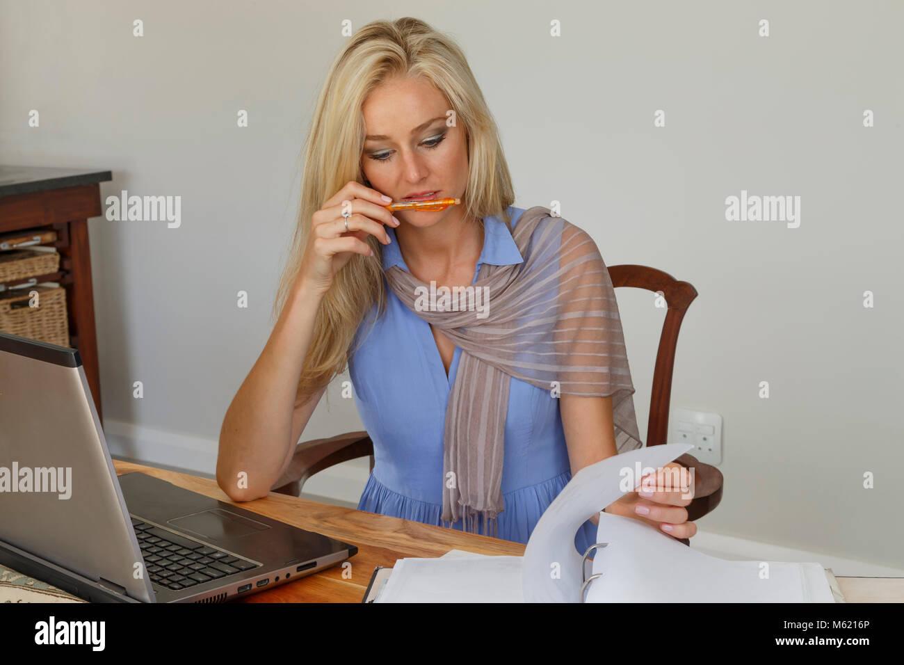 Eine nachdenkliche gut gekleidete junge Frau, die von zu Hause aus arbeiten in entspannter Umgebung tiefer Konzentration Stockbild