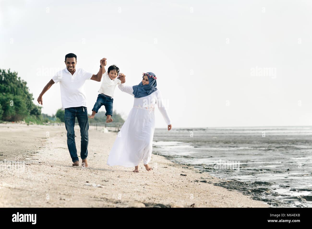 Glückliche Familie Spaß an der schlammigen Strand von Pantai remis, Selangor, Malaysia. Familienkonzept Stockbild
