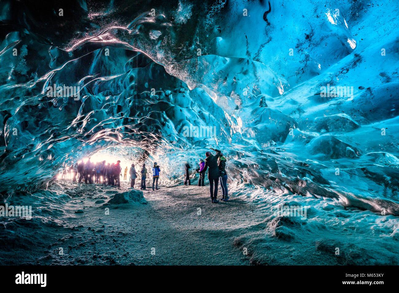 Touristen, die sich in der Crystal Cave, Breidamerkurjokull Gletscher, Island. Emerald Blue Ice und Asche ist Teil Stockbild
