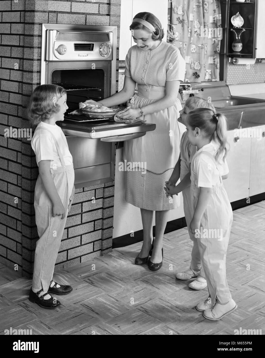 1950s Mutter Und Drei Töchter Die Herumstehen Und Ofen In Der Küche