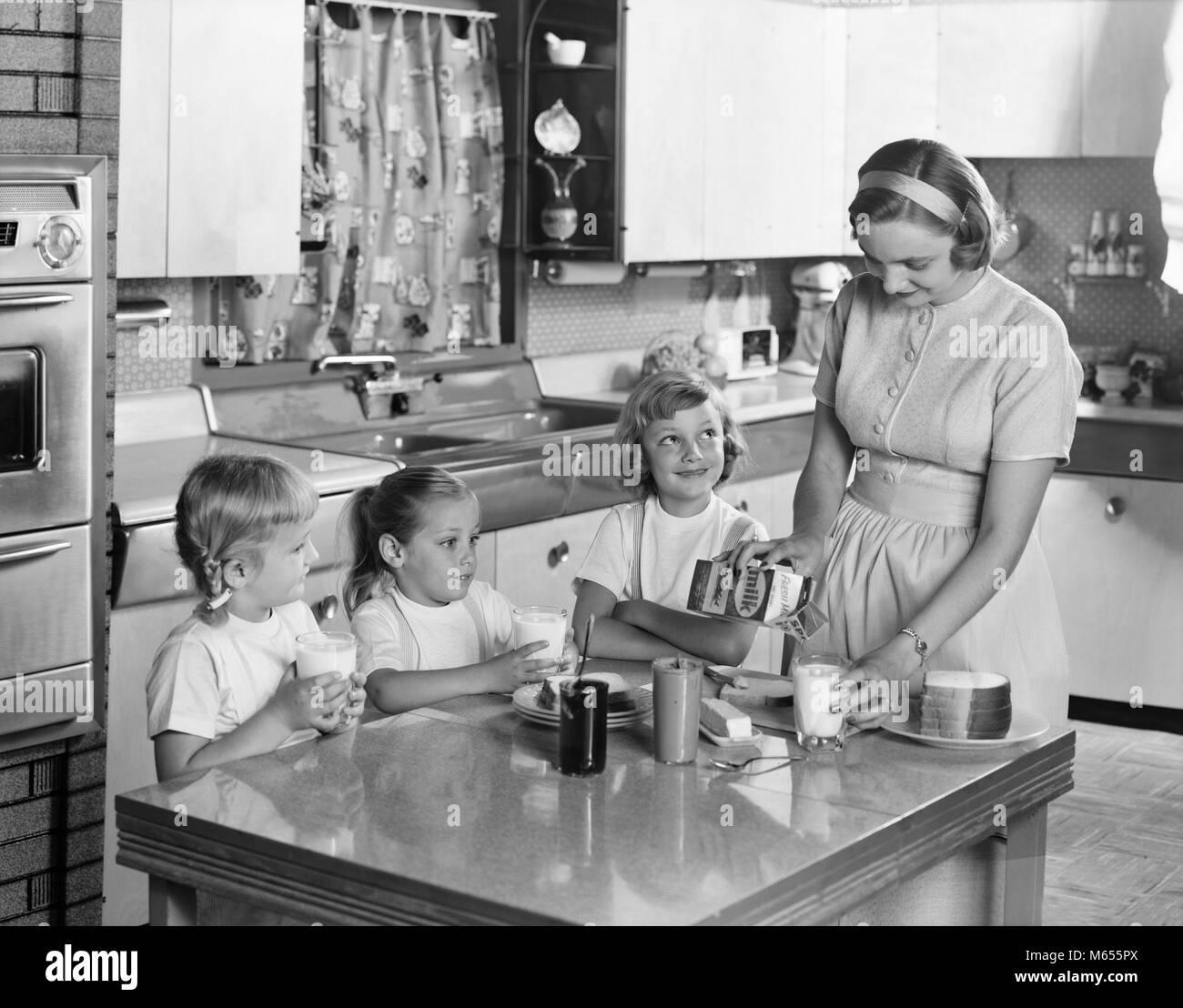 1950 Mutter Von Drei Töchtern Die Herumstehen Und Küche Tisch Macht