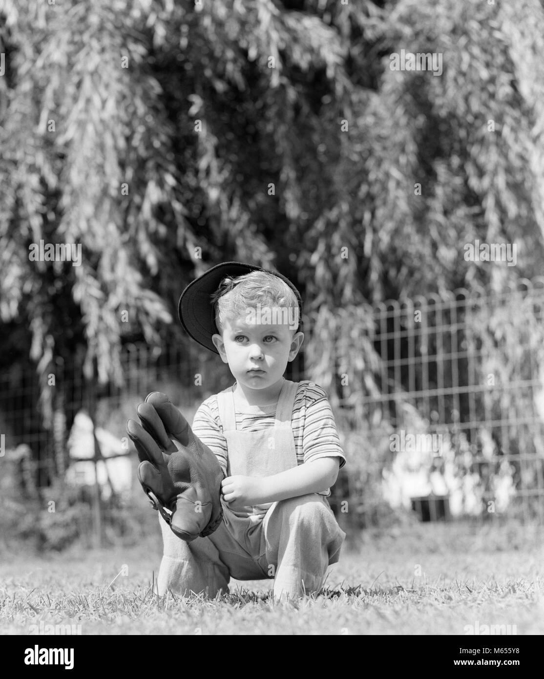1940 Kleine ernsthafte blonde Junge HOLDING EINEN BASEBALL HANDSCHUH TRAGEN BASEBALL CAP IM GRAS-b 18929 HAR 001 Stockfoto