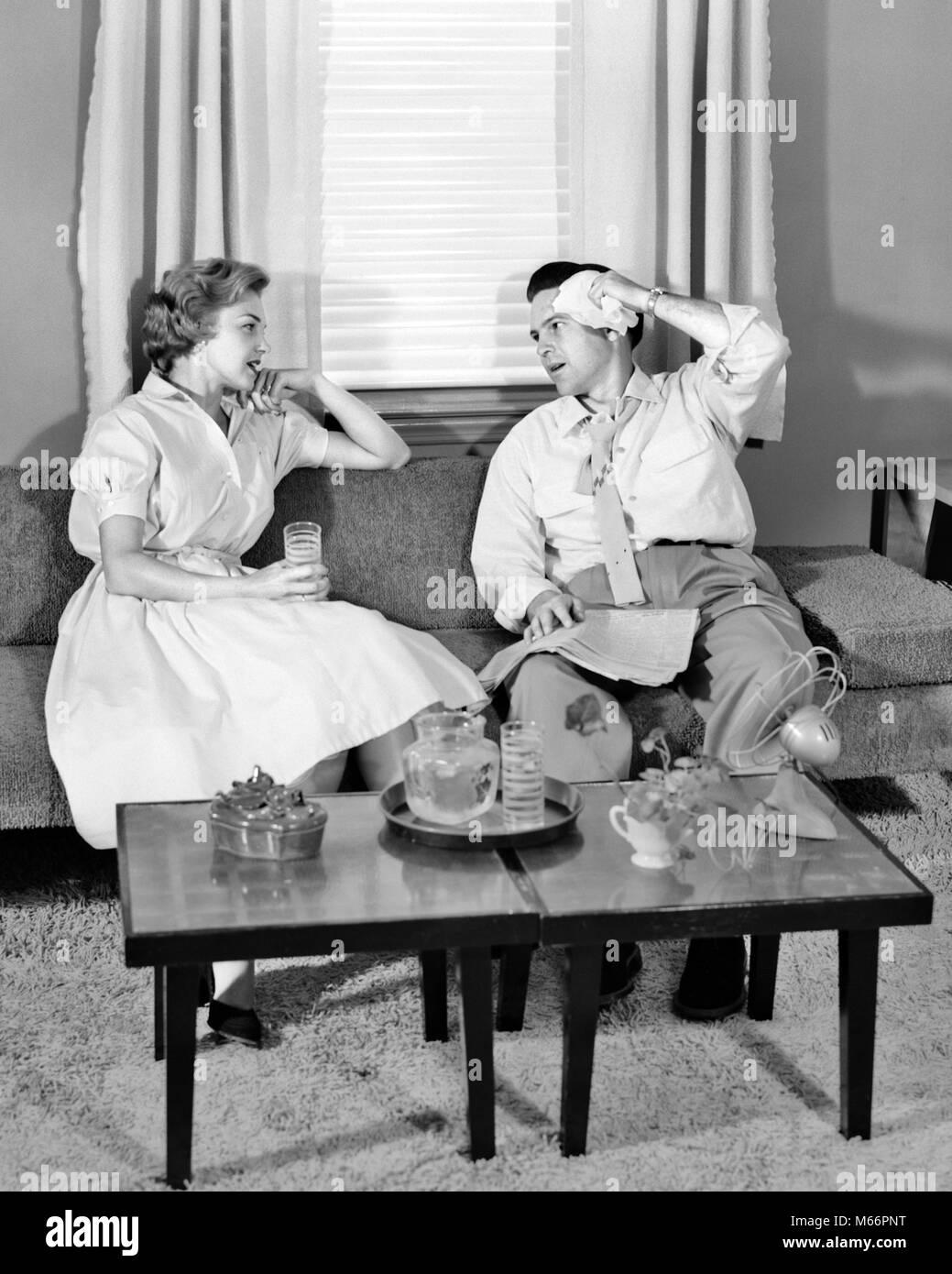 1950s Paar sitzt auf WOHNZIMMER COUCH, ZUM ABKÜHLEN TRINKEN ICED ...