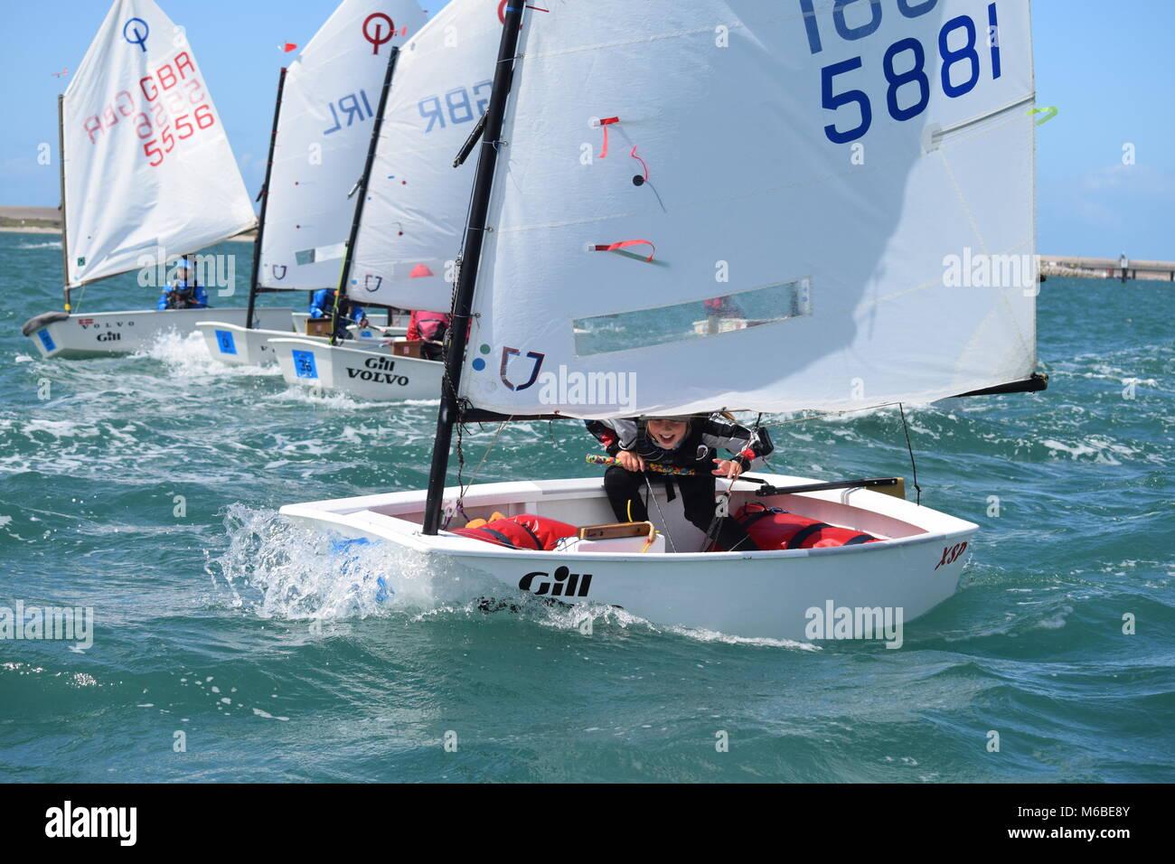 Junior Racing Optimist Segler Jollen in Weymouth Hafen auf einem sonnigen, windigen Tag. Stockbild