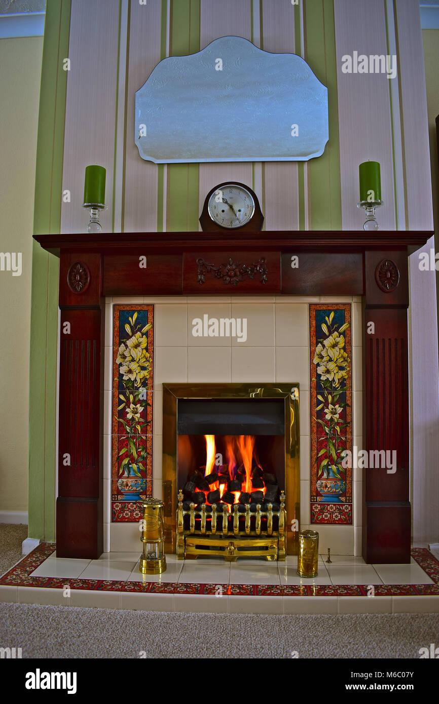 Ein Gemütliches Bild Eines Kohle  Wirkung Gas Feuer Mit Holz Kaminsims Oben  Mit Einem 50er Ära Uhr Durch Zwei Kerzen Flankiert. Messing Miners Lamp  Unten.