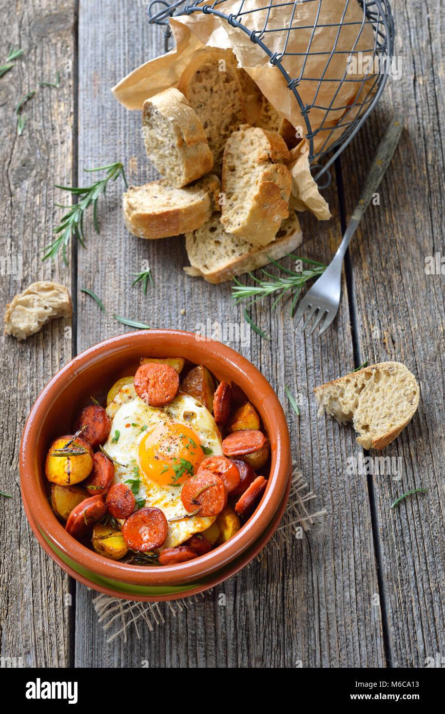Spanische Tapa: Würzig Chorizo Wurst mit Spiegelei und Kartoffeln in einem Terra Cotta cazuela Gericht serviert. Stockfoto