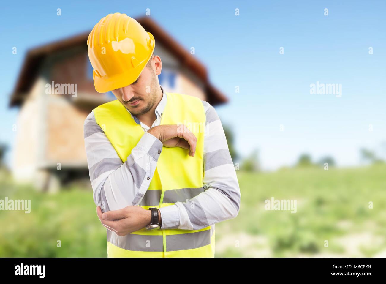 Arbeitsunfälle und schmerzhaften Winkelstück Konzept mit Builder auf im Hintergrund mit neuen im Bau Haus Stockbild