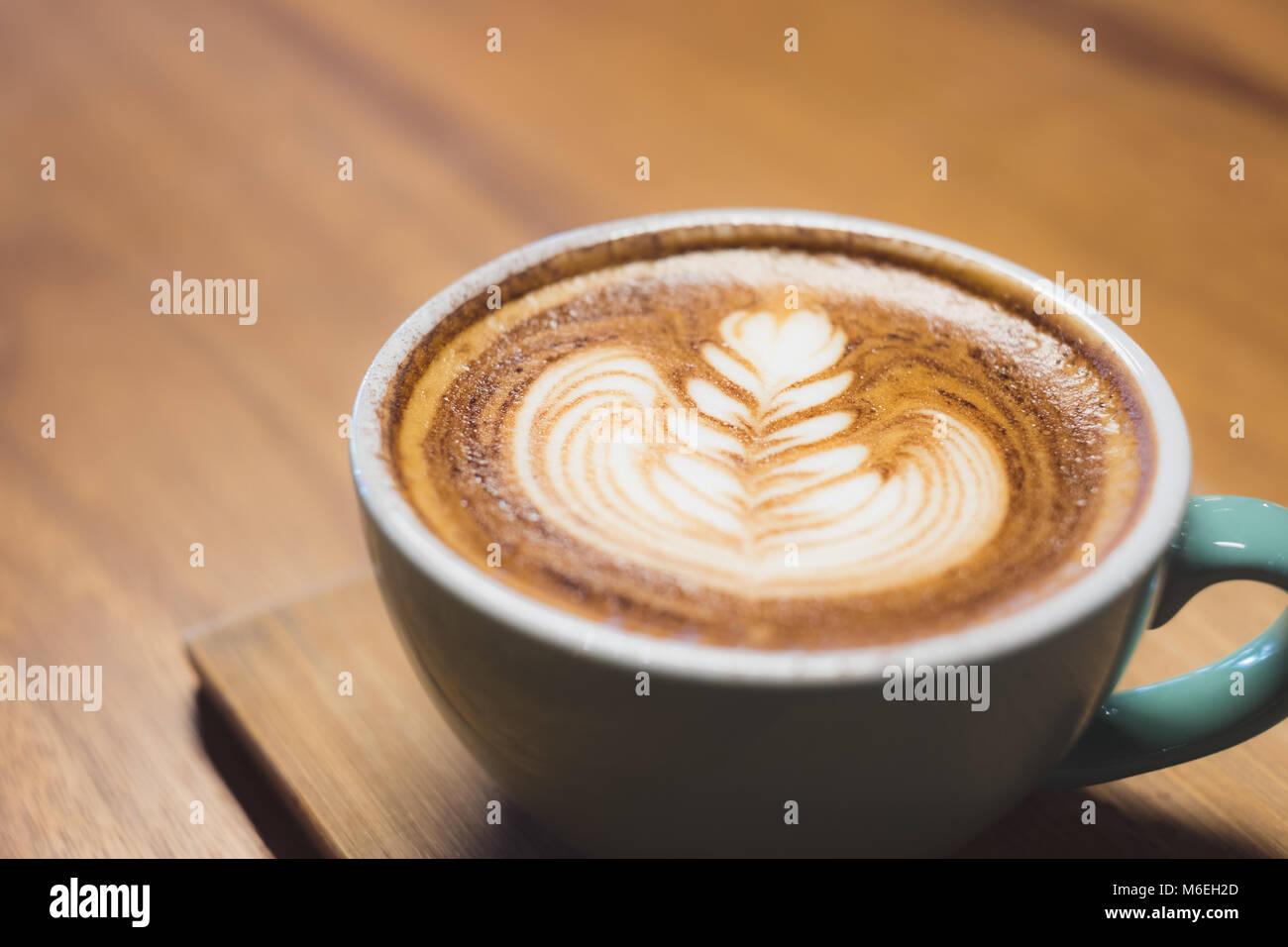 Close up heißen Cappuccino Tasse mit Herzform latte Kunst auf Holz Tisch im Cafe, Drak Tone Filter, Essen und Stockbild