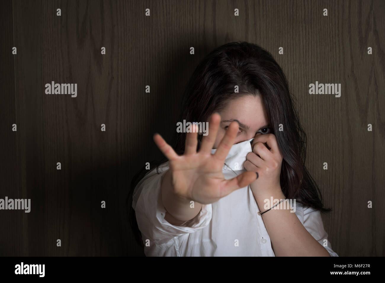 Junge Frau versteckt sich ihr Gesicht mit ihrem Hemd, während ihre Hand, die sich auf die Kamera zu, um nicht Stockbild