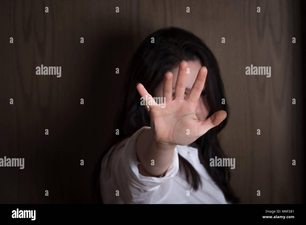 Brünette Frau, die ihre Hand, die sich auf die Kamera gestreckt, die ihr Gesicht, ohne gesehen zu stoppen oder Stockbild