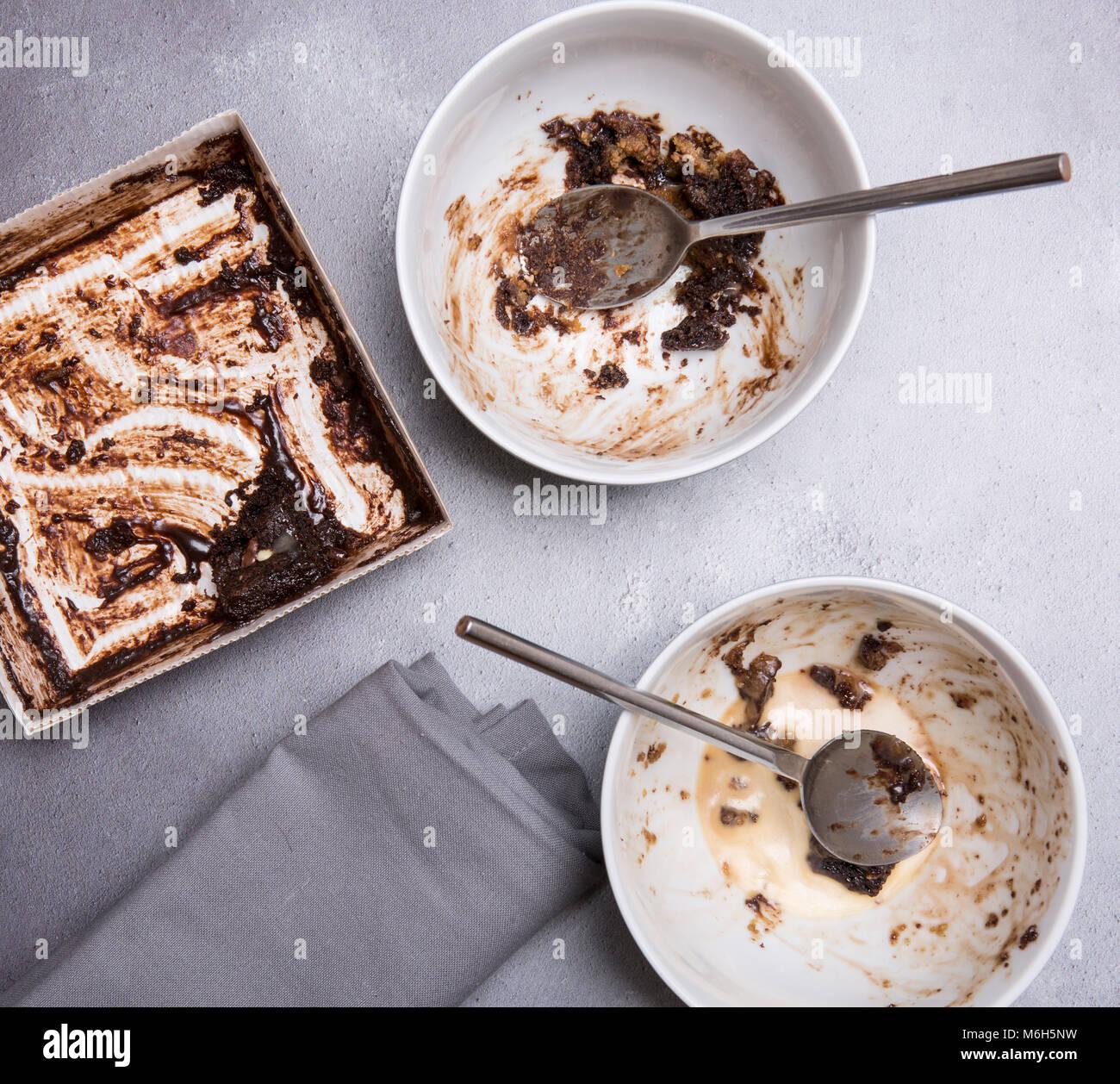 Schokoladenpudding Reste auf einem grauen strukturierten Hintergrund mit mapkin Löffeln und Schalen Stockbild