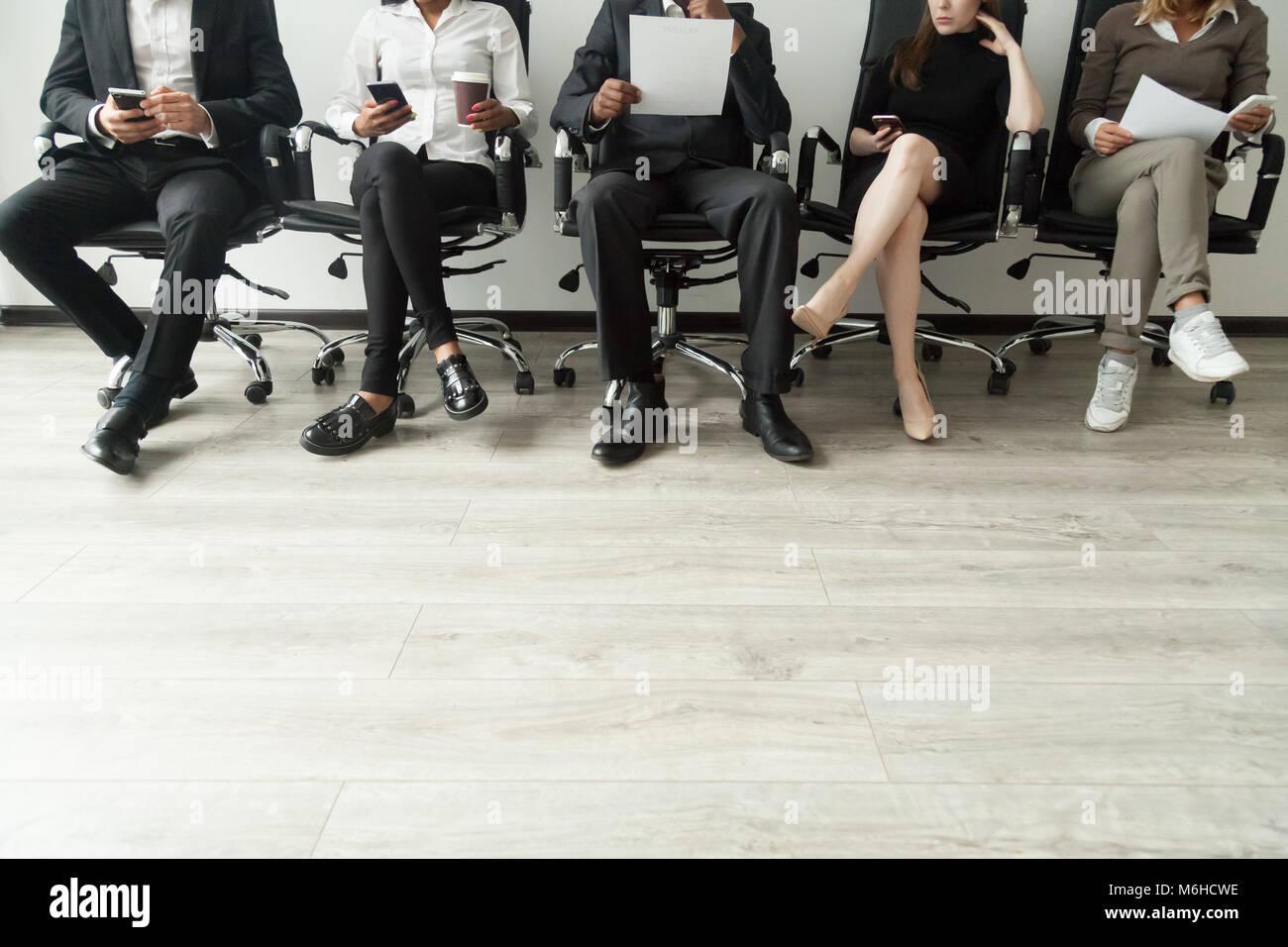 Diverse Geschäftsleute in der Warteschlange holding Smartphones warten und Stockbild