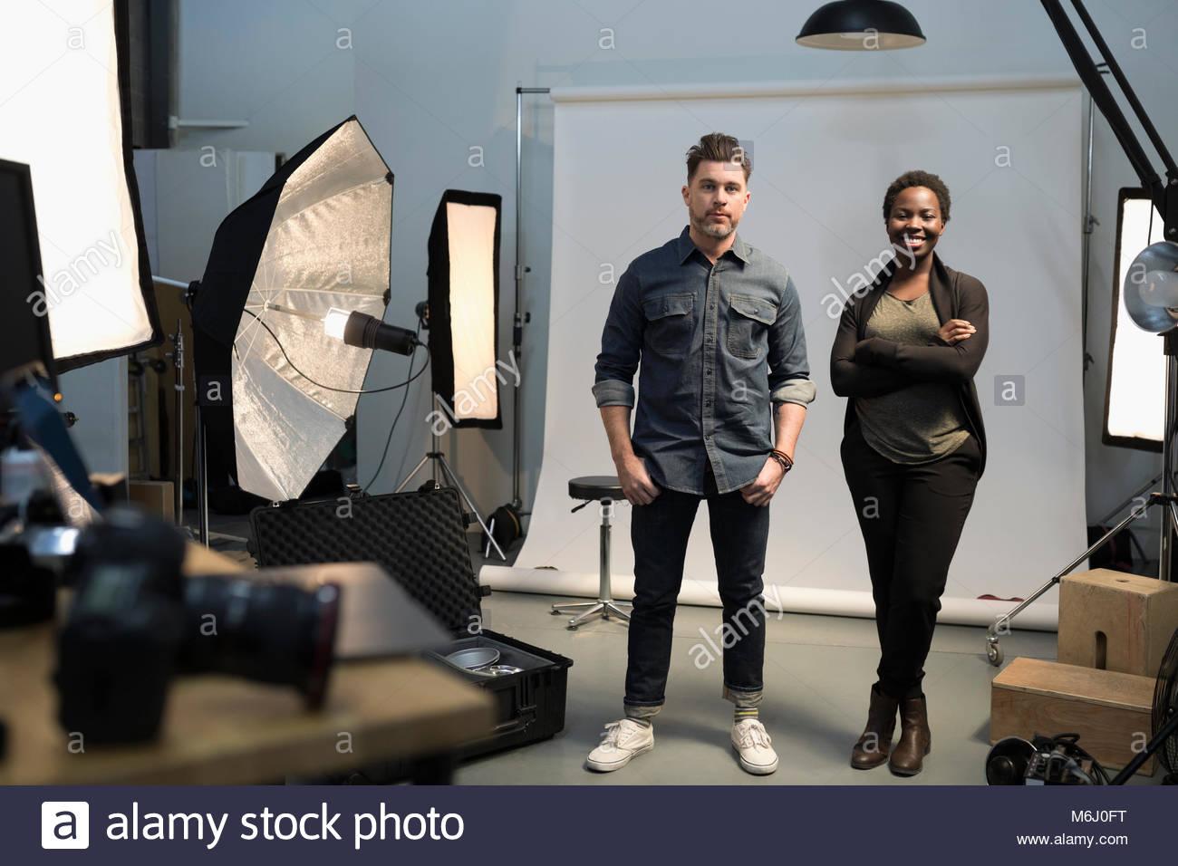 Portrait zuversichtlich Fotografen mit Ausrüstung, bereit für Fotoshooting im Studio Stockbild