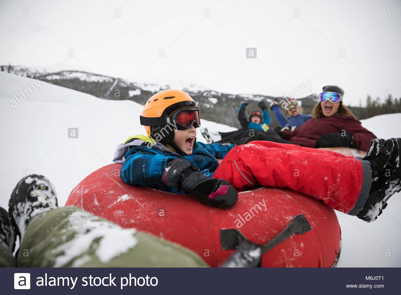 Verspielte junge innere Schläuche mit Familie im Schnee auf der Tube Park Stockbild