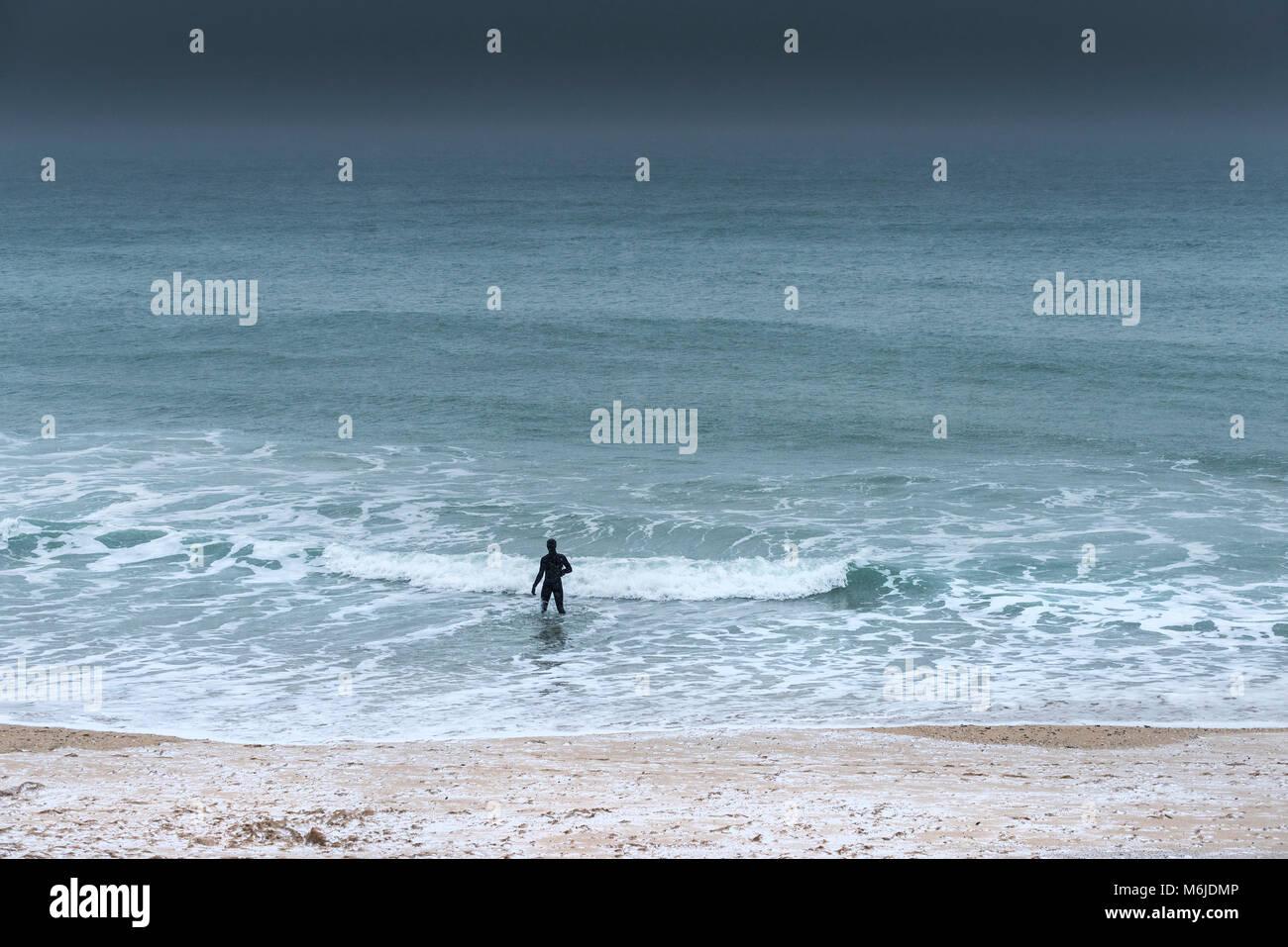 Eine Abbildung in einem Neoprenanzug zu Fuß ins Meer während eiskalt Wetter. Stockbild